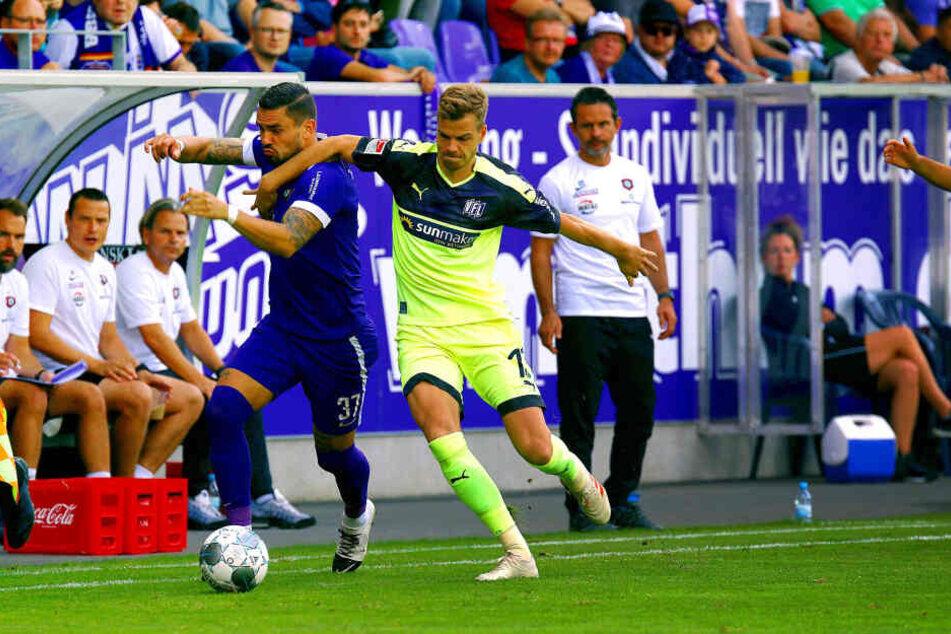 Pascal Testroet (l.) setzt sich energisch gegen Onsabrücks Joost van Aken durch - Aues Trainer Dirk Schuster (r.) hat die Aktion genau im Blick.