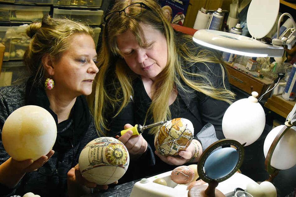 Die Hobby-Ostereiermalerin Susanne Liebscher (l.) arbeitet mit Kerstin Dischereit in deren kleinen Ostereier-Werkstatt an der Gestaltung von verschiedenen Nandu- und Straußeneiern.