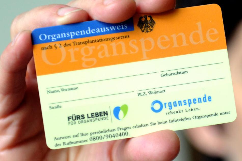 Ein Organspendeausweis wird in der Hand gehalten.