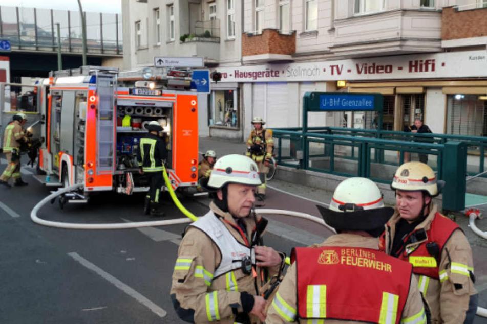 Berliner Feuerwehrmänner beraten sich vorm Eingang zum U-Bahnhof Grenzallee.