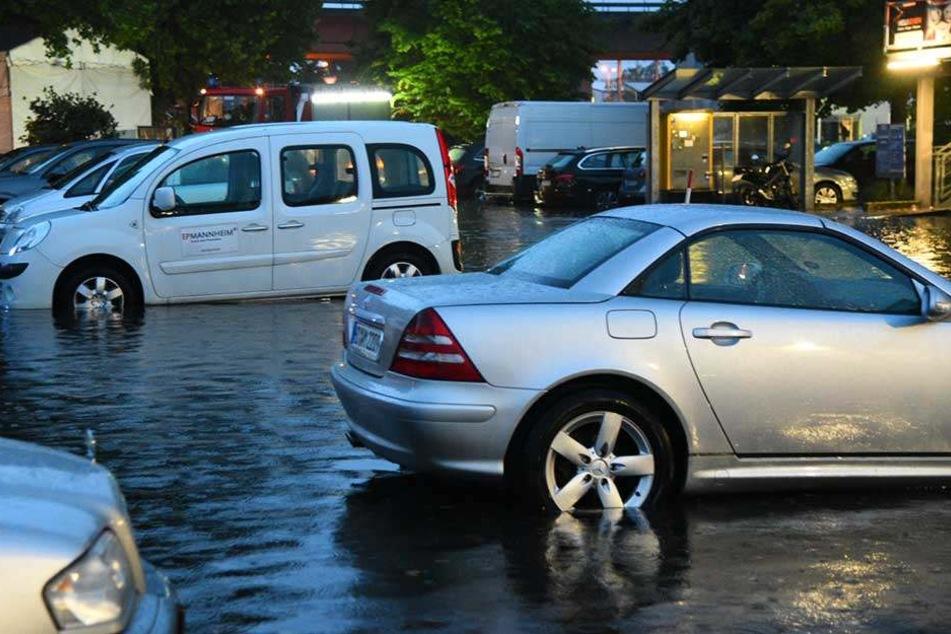 Nach einem schweren Gewitter mit Starkregen stehen Autos auf einem teilweise überflutetem Parkplatz in Mannheim.