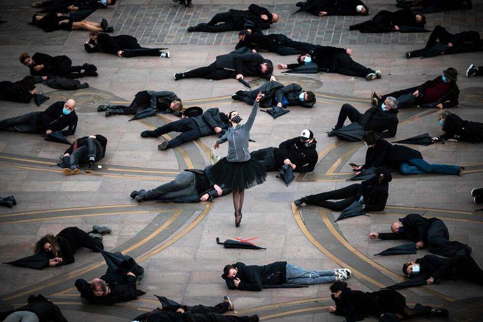 """Demonstranten liegen bei einem Protest gegen die Schließung von """"nicht notwendigen"""" Geschäften während der Corona-Pandemie auf dem Boden."""