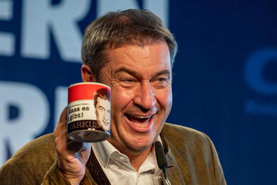 """Markus Söder freut sich beim Politischen Frühschoppen Gillamoos über eine Tasse mit der Aufschrift """"Schön dass es mich gibt! Markus""""."""