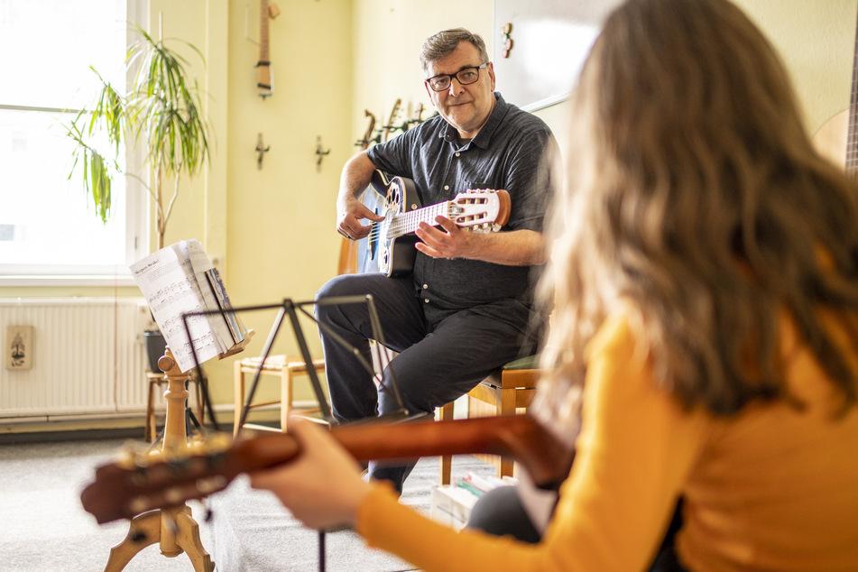 Ein Lehrer bringt in einer Musikschule seiner Schülerin das Spielen einer Gitarre bei.