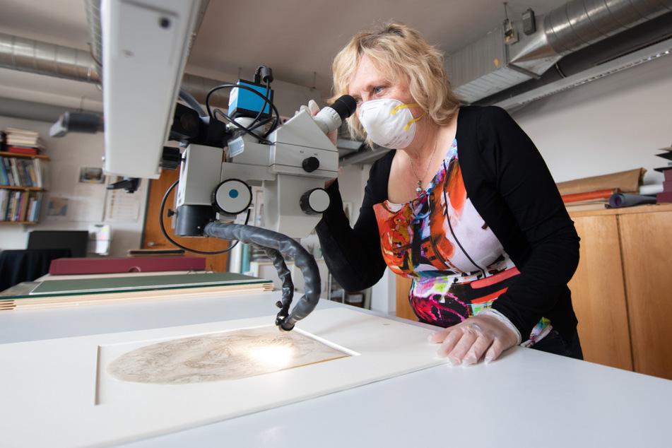 """Wiebke Schneider, Restauratorin Kupferstich-Kabinett, inspiziert in der Restaurierungswerkstatt des Kupferstich-Kabinetts mit einem Mikroskop die Zeichnung """"Allegorie des Schlafs"""" von Taddeo Zuccari."""