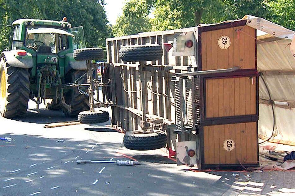 Ein Planwagen liegt umgekippt auf der Straße, hinter einem Traktor.