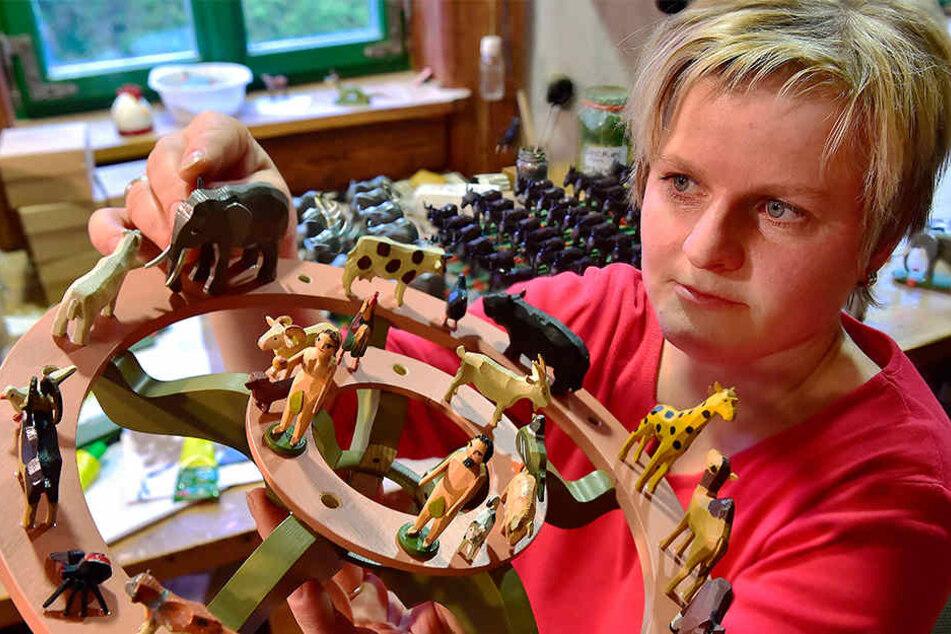 Spielzeugmacherin Tabea Drechsel ordnet in der Seiffener Werkstatt Werner Figuren auf einer Leuchter-Etage an