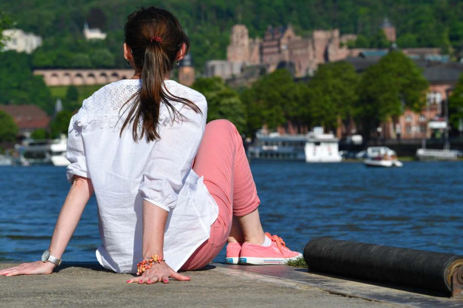 Eine junge Frau sitzt in Heidelberg am Ufer des Neckar und blickt auf die Schlossruine und Teile der Altstadt.