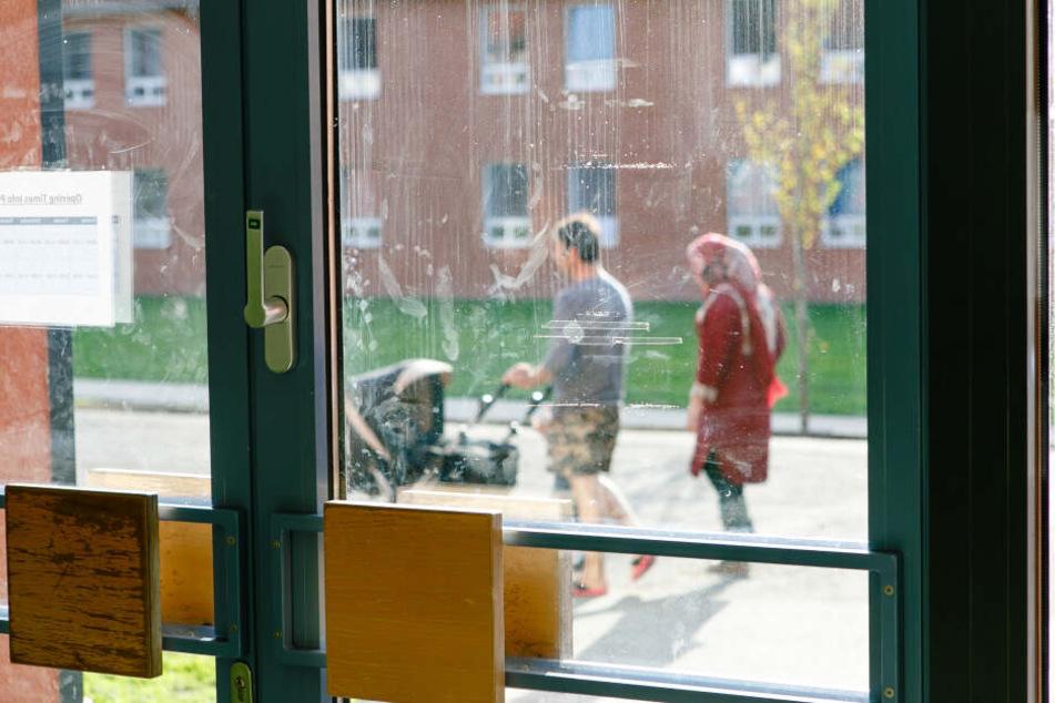 Eltern schieben beim Spaziergang einen Kinderwagen in einer Flüchtlingsunterkunft im schleswig-holsteinischen Boostedt.