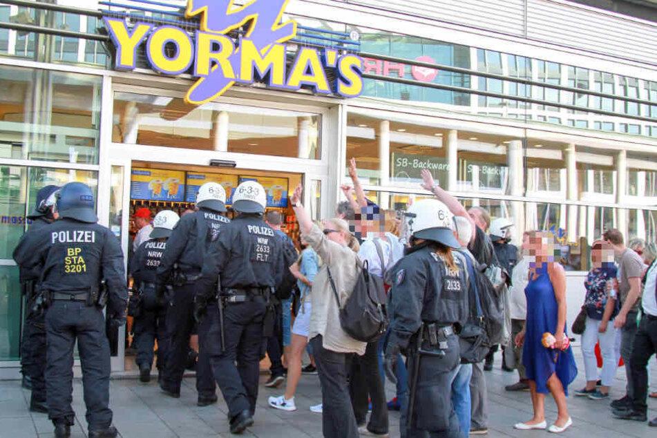 Die rechtsgerichteten Demonstranten werden durch einen Supermarkt in das Bahnhofsgebäude gelotst. Einige winken hämisch in Richtung der Gegendemonstranten.