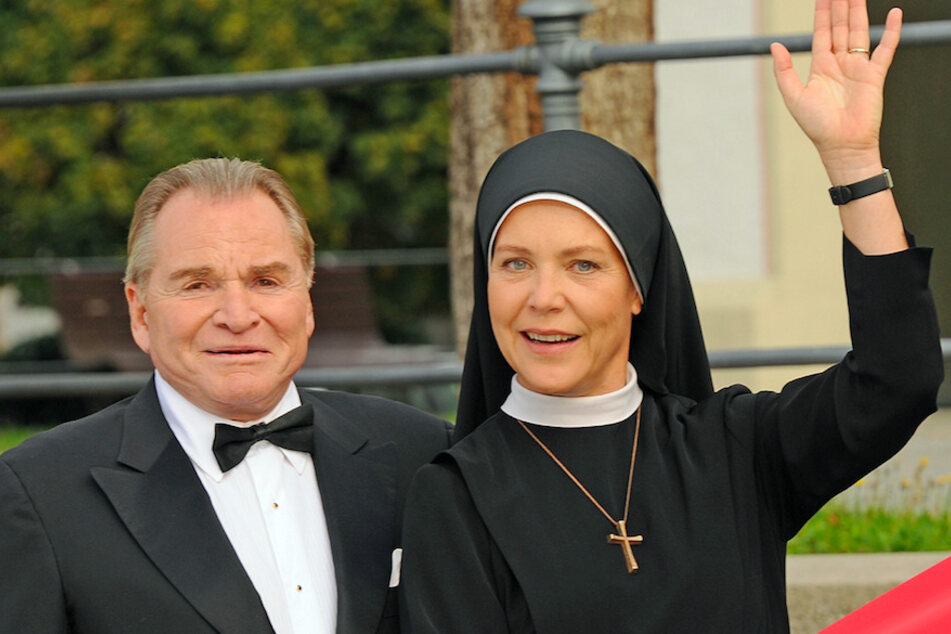 """Die Schauspieler Fritz Wepper (als Bürgermeister Wolfgang Wöller) und Janina Hartwig (als Schwester Hanna) lächeln in einer Pause während der Dreharbeiten der ARD-Fernsehserie """"Um Himmels Willen""""."""