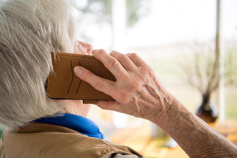 Eine Seniorin telefoniert mit ihrem Smartphone: Bei Betrugsmaschen werden oft ältere Menschen Opfer. (Symbolbild)