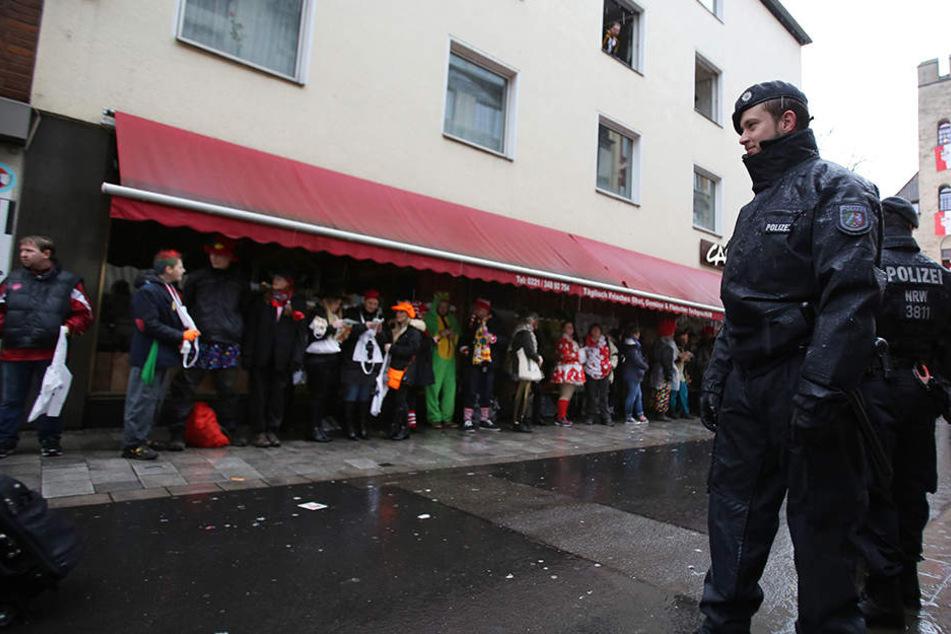Polizisten und Narren stehen am Rosenmontag 2016 in Köln im Regen.