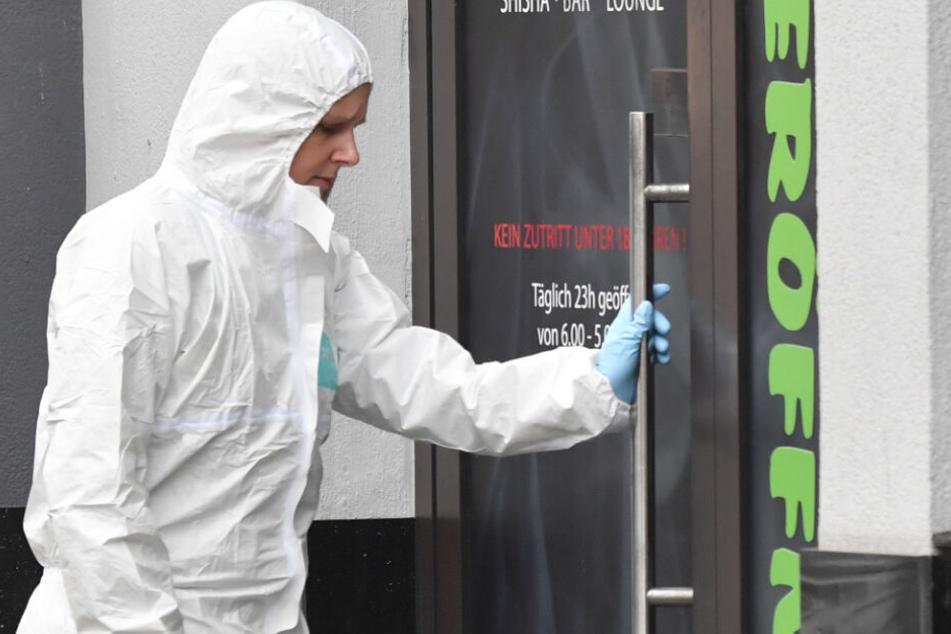 Eine Mitarbeiterin der Spurensicherung steht an einem Tatort am Heumarkt in Hanau.