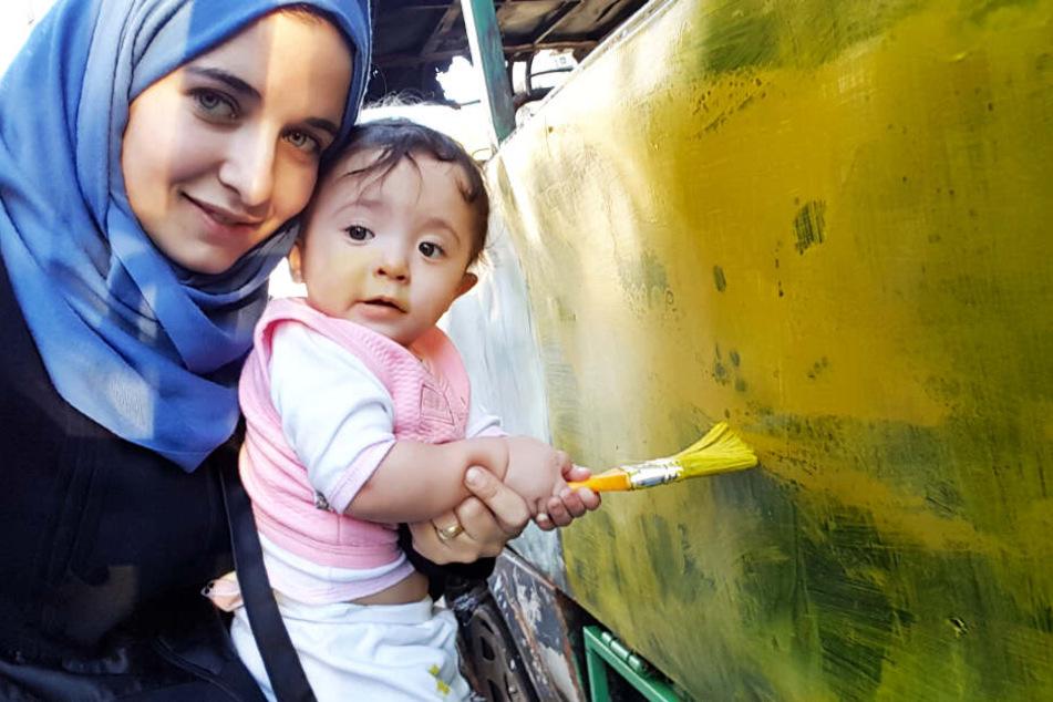 Den Kriegsalltag durchbrechen die Menschen immer wieder mit schönen Szenen. Hier malt Waad Al-Kateab mit ihrer Tochter Sama einen Bus an.