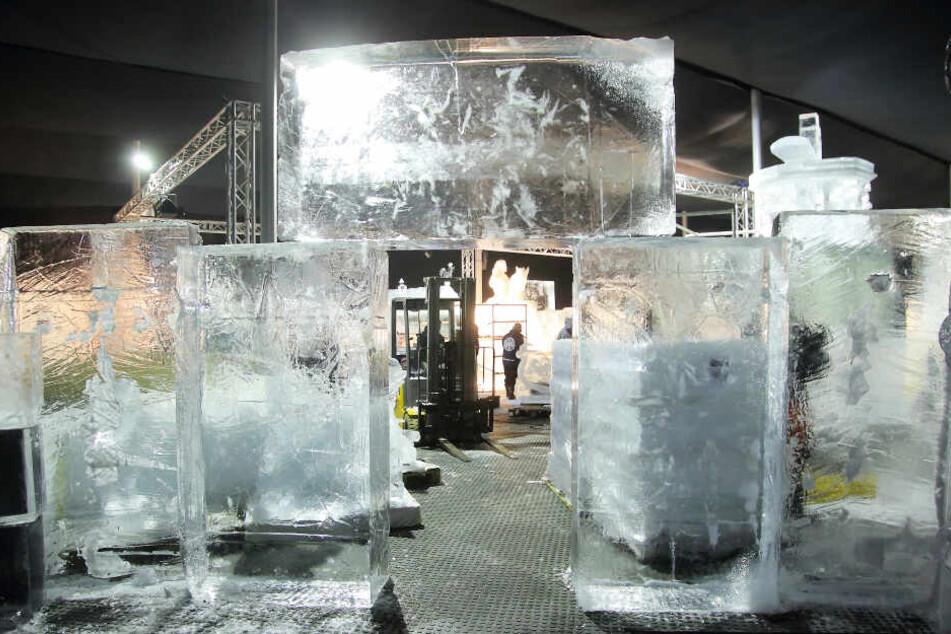 Die noch unbearbeiteten Eisblöcke stapeln sich zu einem Tor. Die ersten Umrisse erhalten sie mit der Kettensäge.