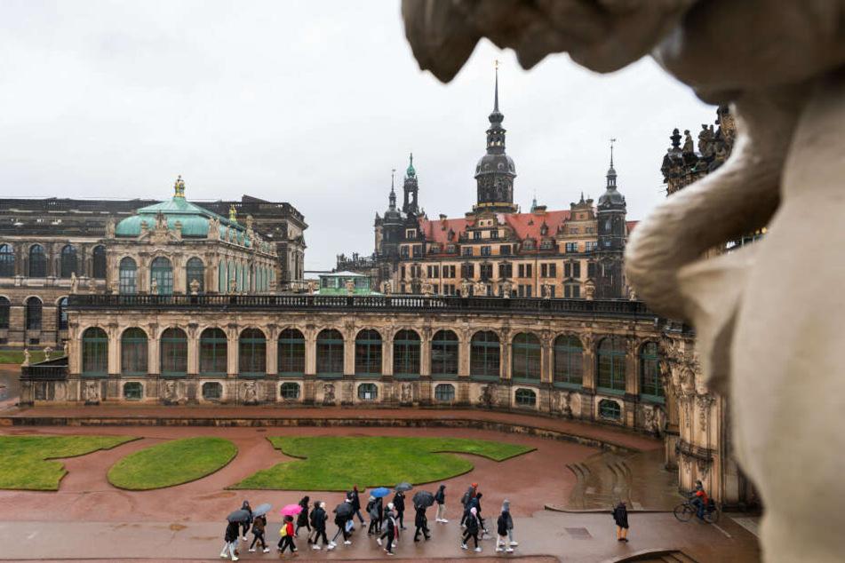 Touristen gehen bei Regen durch den Dresdner Zwinger. Im Hintergrund ist das Residenzschloss und der Hausmannsturm zu sehen.