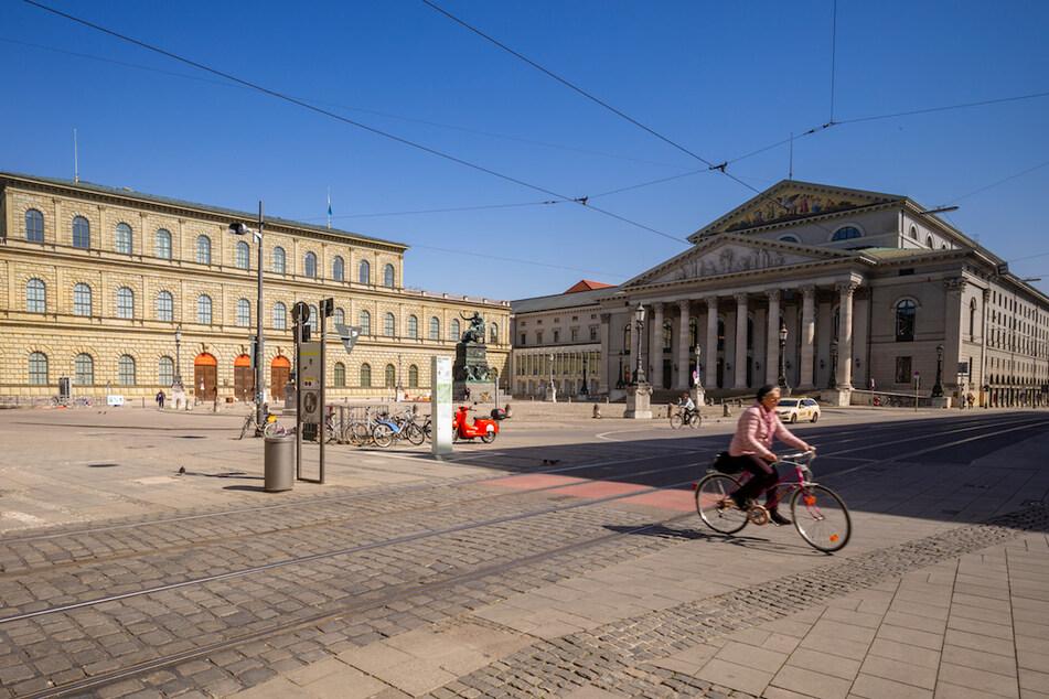 Eine Radfahrerin fährt über den fast menschenleeren Max-Joseph-Platz; links der Königsbau und rechts die Bayerische Staatsoper.