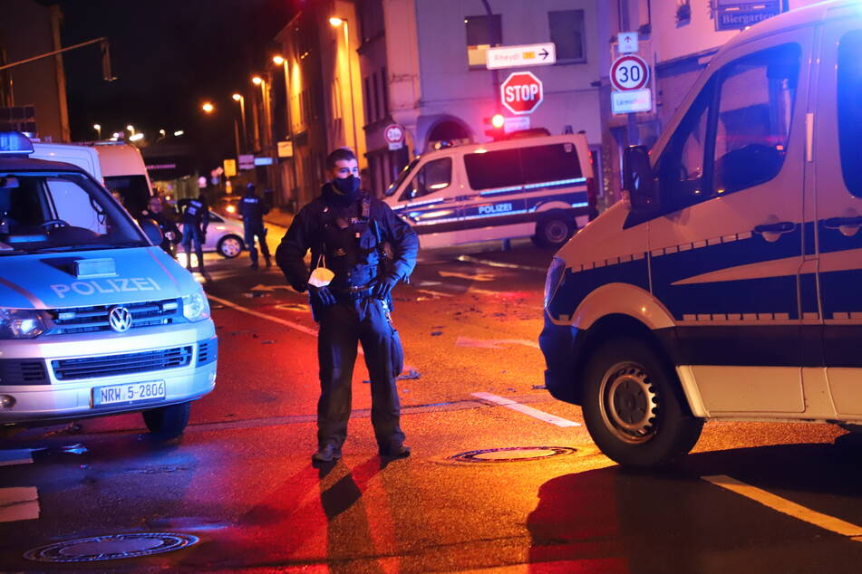 Polizisten sichern eine Straße während einer Hausdurchsuchung in Mönchengladbach.