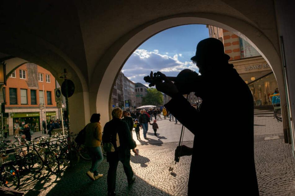 Ein Straßenmusiker spielt in der Fußgängerzone in der Münchner Innenstadt auf seiner Geige.