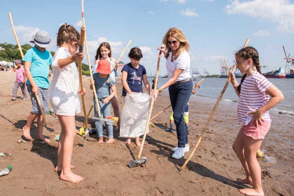Zusammen mit Kindern sammelt Frauke Ludowig Müll am Elbstrand.