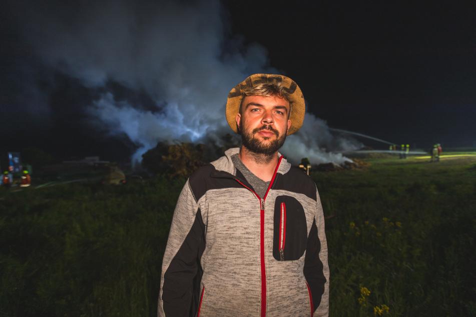 Landwirt Marcel Schaller steht vor seinen brennenden Strohballen. Auf den Landwirt bzw. seine Fahrzeuge sollen laut eigener Aussage in den vergangenen Wochen mehrere Anschläge verübt worden sein. Im jüngsten Fall brannte eine Scheune vollständig ab.