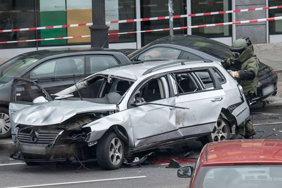 Ein Sprengstoffexperte der Polizei nähert untersucht im Schutzanzug das Auto nach weiteren Sprengsätzen.