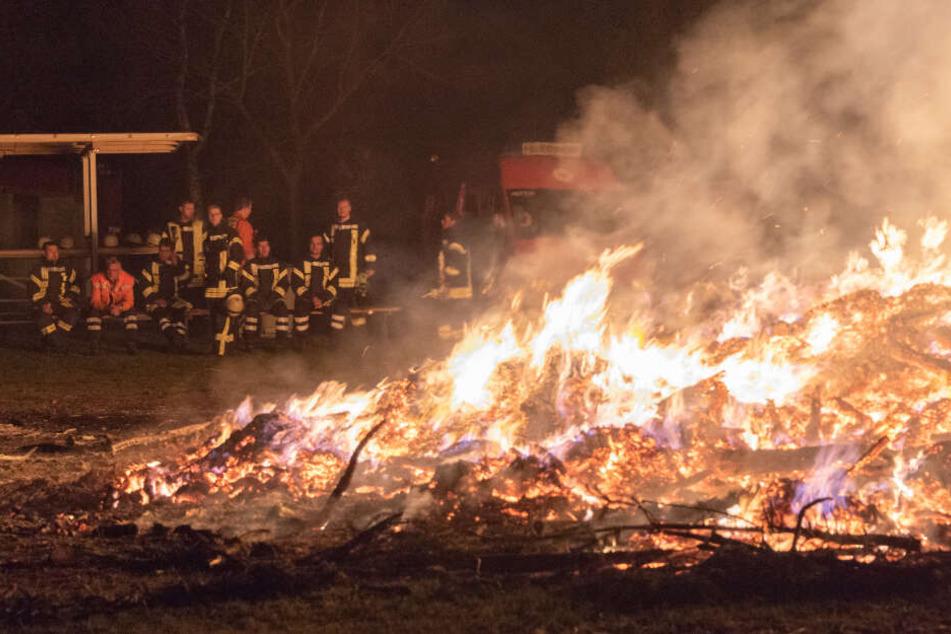 Die Einsatzkräfte schauen beim Abbrennen des Osterfeuers zu.