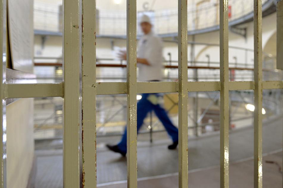 Ein Häftling geht an einer Gittertür in der JVA Moabit vorbei.