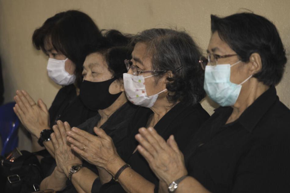 Menschen mit Gesichtsmasken nehmen an der Beerdigungszeremonie eines 35 Jahre alten Thailänders teil, der an Dengue-Fieber litt und sich später mit Covid-19 infizierte.