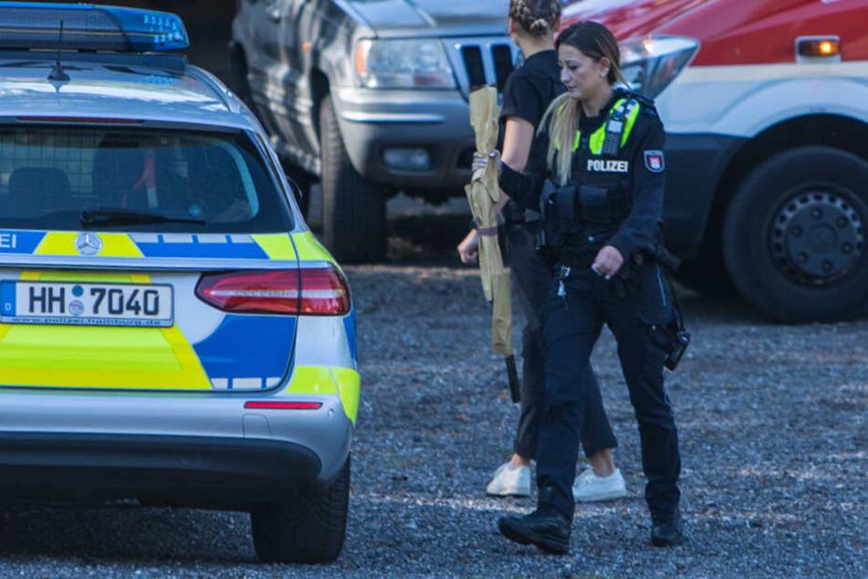 Eine Polizisten stellt das Gewehr des Mannes sicher.