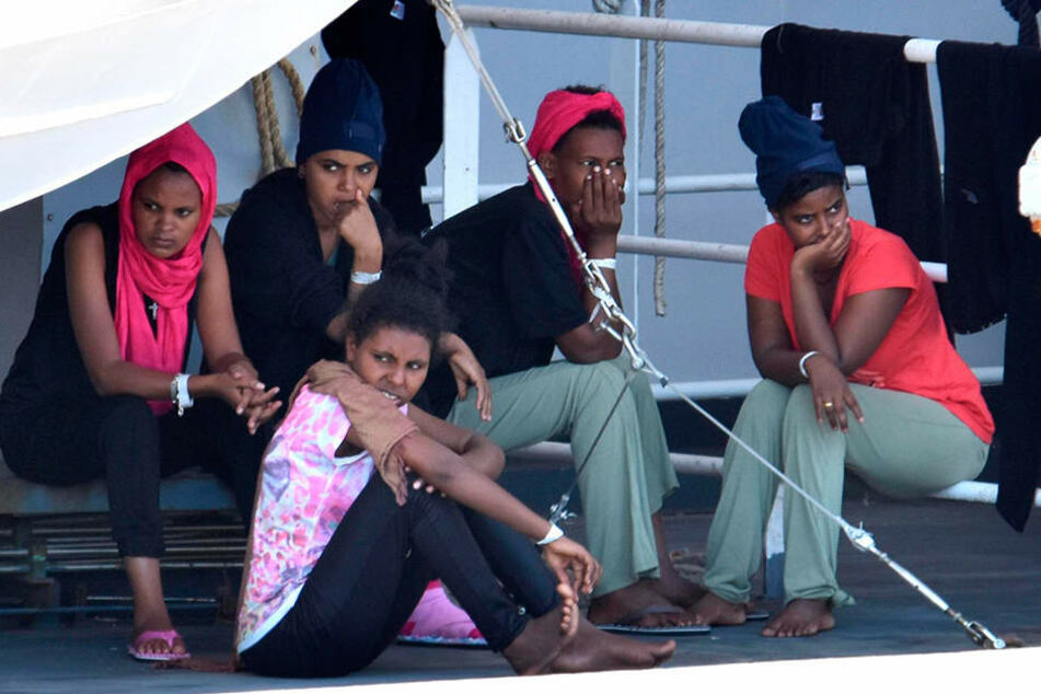 "Migranten an Bord der ""Diciotti"" sitzen im Hafen von Catania (Italien)."