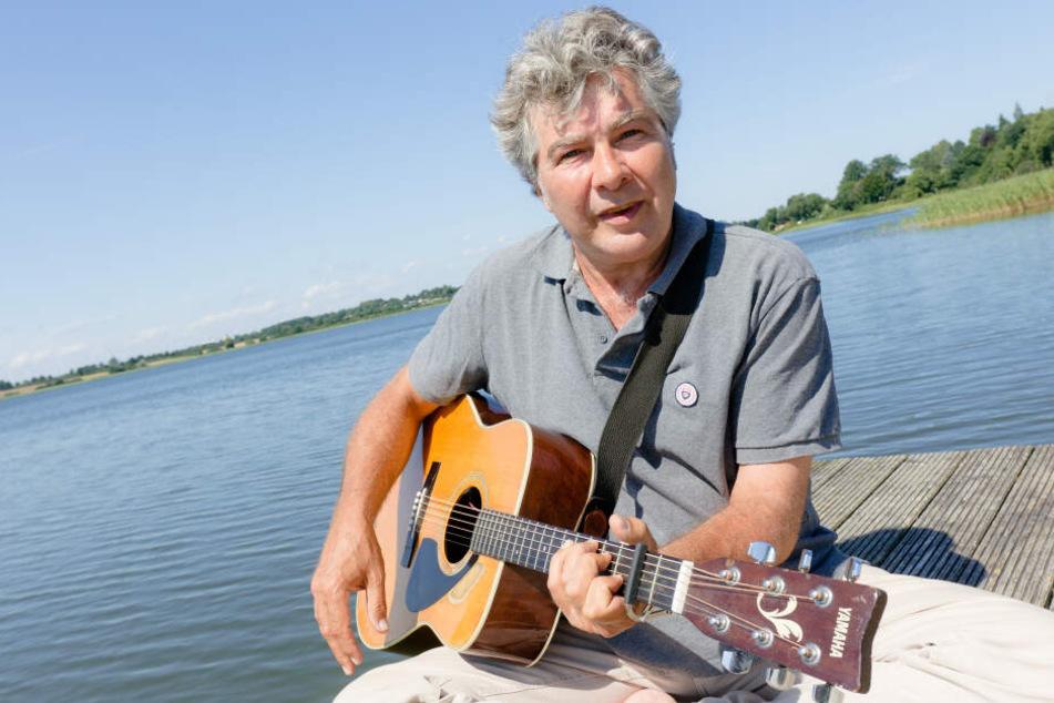 Der Autor Wolfram Eicke spielt am Dienstag auf einem Anleger am Großen Pölitzer See Gitarre.