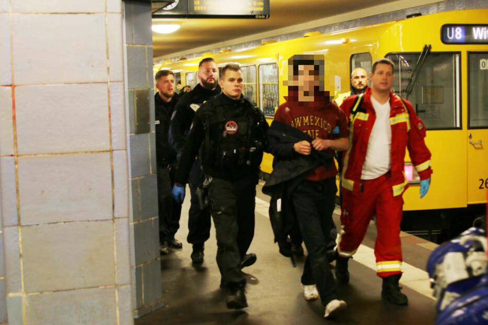 Polizisten und Sanitäter begleiten den verwirrten Mann ins Freie.