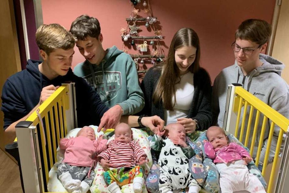 Die 18-jährigen Vierlinge (hinten l-r) Thomas, David, Laura und Florian, schauen sich die kleinen Vierlinge (l-r) Ina, Hanna, Noah und Finja an.