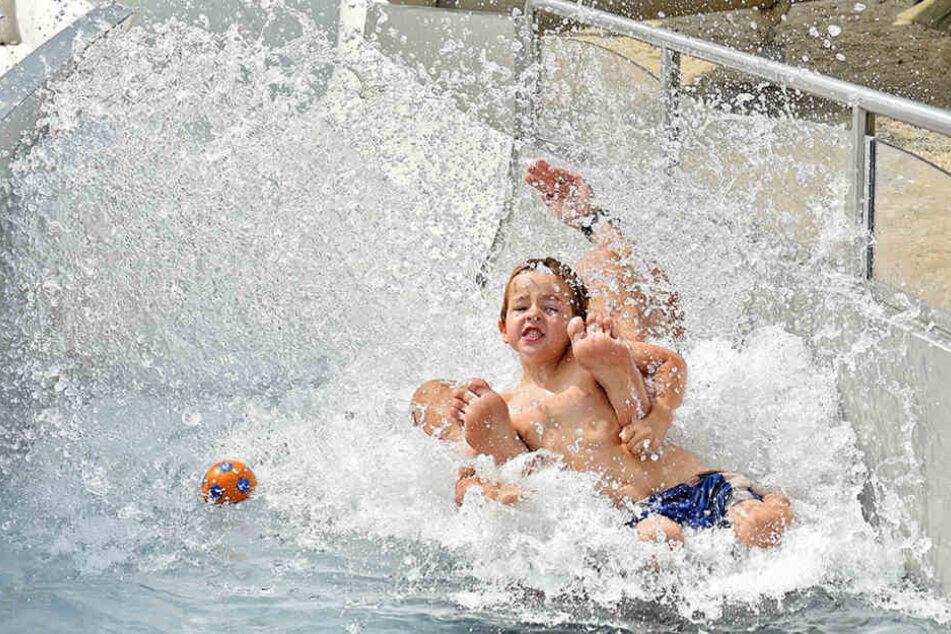 So lässt sich der Hitze-Sommer 2018 ertragen: Kinder rutschen im Freibad Cossebaude von der längsten Freibad-Rutsche der Stadt.