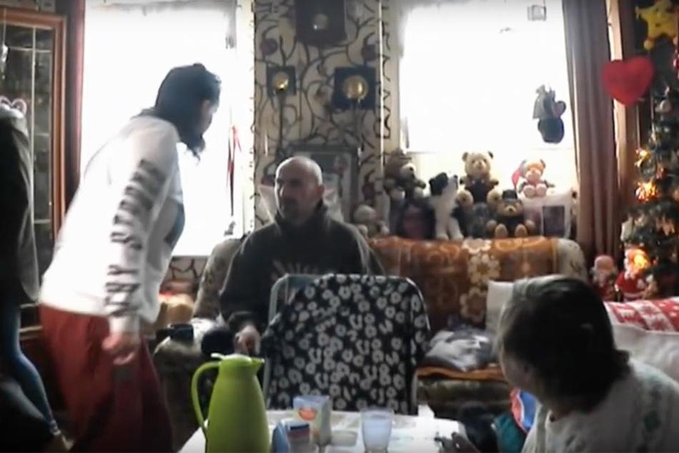"""Nachdem Karins Tochter Yvonne (weißer Pullover) die Schnapsflasche von ihrem Bruder Norman (sitzend) versehentlich umgestoßen hat, rastet der aus. Mutter Karin kündigt an: """"Der geht heute weg hier, der ist eine Gefahr für die Menschheit""""."""