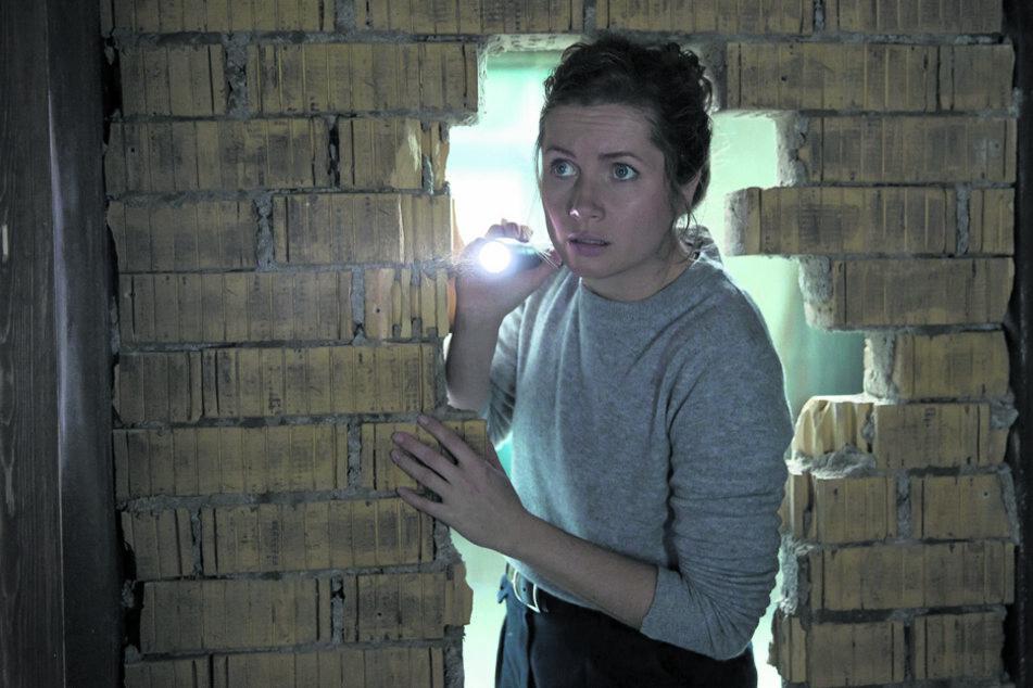 Leonie Winkler (Cornelia Gröschel) leuchtet mit einer Taschenlampe in den dunklen Raum hinter der Mauer.