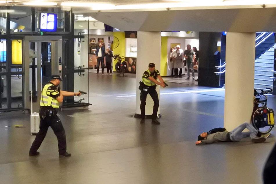 Polizisten richten die Waffe auf den Mann, den sie zuvor angeschossen haben. Er stach zuvor zwei Menschen mit einem Messer nieder.