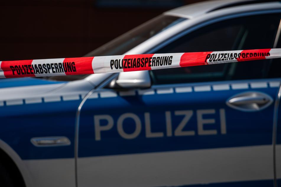 Ein Polizeiauto steht hinter einem Absperrband der Polizei. (Symbolbild)