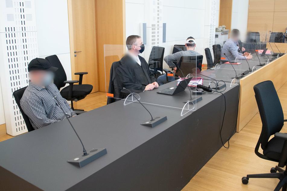Die Angeklagten (l., 3.v.l. und 5.v.l.) sitzen mit ihren Verteidigern im Landgericht Dresden.