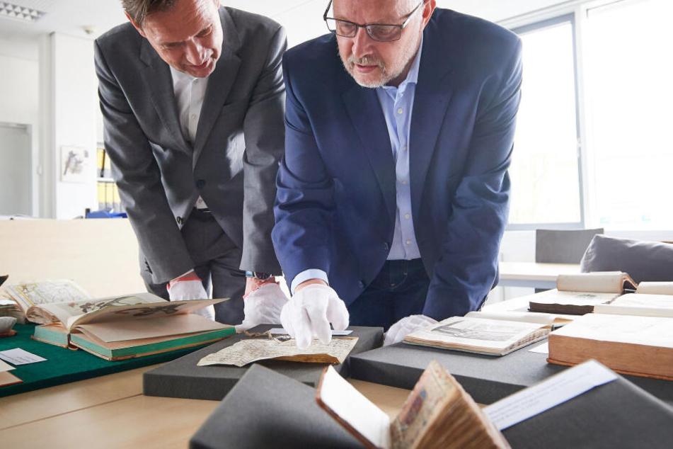 Ulrich Meyer-Doerpinghaus (l), Direktor der Universitäts- und Landesbibliothek Bonn, und Dezernent Michael Herkenhoff, schauen auf Bücher aus dem Vorkriegsbestand.