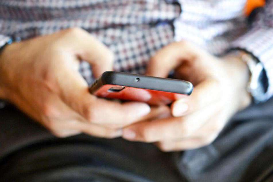 Ein Mann schreibt eine Nachricht auf seinem Smartphone (Symbolbild).