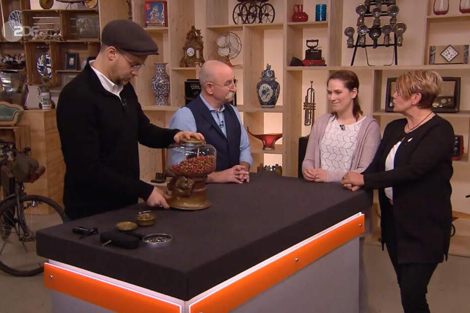 Experte Fabian Benöhr (li.) begutachtet die Nuss-Glocke, während sich Hort Lichter (2.v.li.) mit Elena Glaw (2.v.re.) und ihrer Mutter Susanne (re.) unterhält.