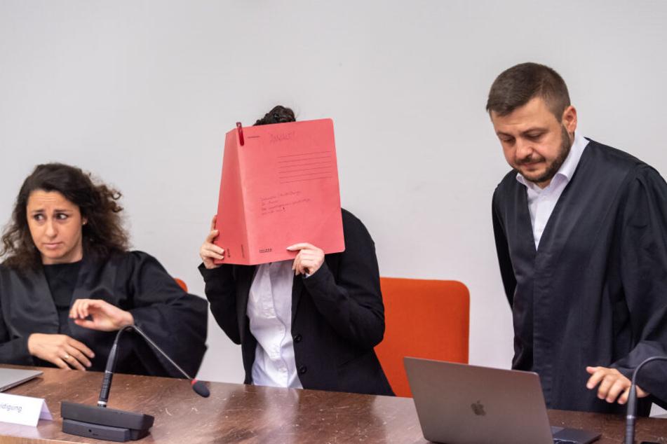 Die Angeklagte hält sich vor Verhandlungsbeginn im Gerichtssaals einen roten Aktendeckel vors Gesicht. Neben ihr sind ihre Anwälte Sera Basay-Yildiz (l) und Ali Aydin (r).