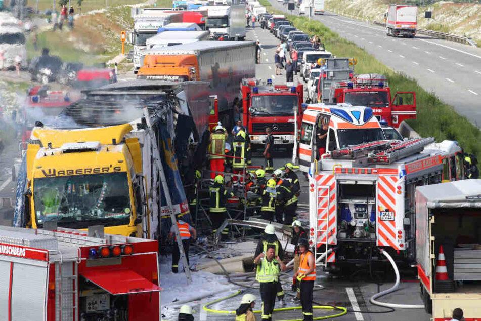 Feuerwehrleute arbeiten auf der Autobahn 9 bei Schleiz im Saale-Orla-Kreis an einem brennenden Lastwagen.