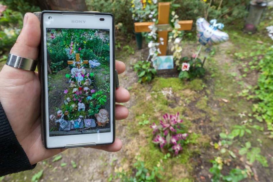 Antje Emmerlich zeigt ein Handybild, auf dem das Grab mit Blumenschmuck zu sehen ist.