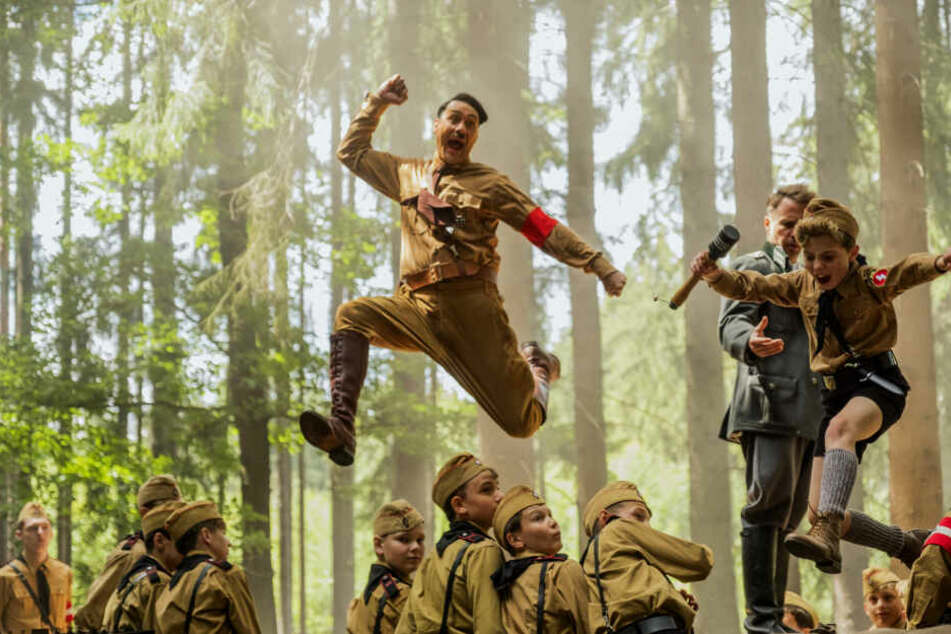 """Johannes """"Jojo"""" Betzler (r., Roman Griffin Davis) klaut Captain Klenzendorf (Zweiter von rechts, Sam Rockwell) angestachelt von Adolf Hitler (oben, Taika Waititi) eine Granate aus der Hand."""