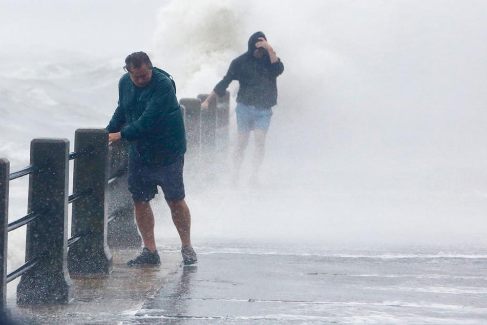 Fußgänger in Charleston, South Carolina, erwischten die Wellen. Mittlerweile ist Irma vom Hurrikan zum tropischen Tief herabgestuft.
