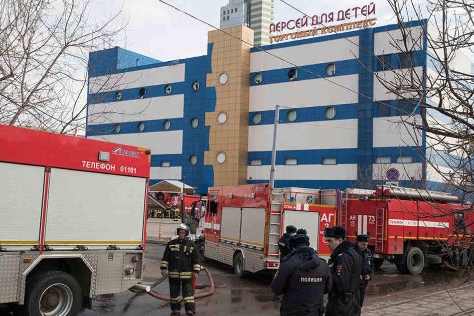 Löschfahrzeuge stehen nach einem Brand in einem Moskauer Einkaufszentrum vor dem Gebäude.